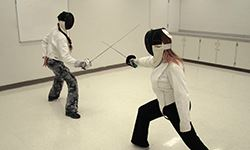 Two adults foil fencing